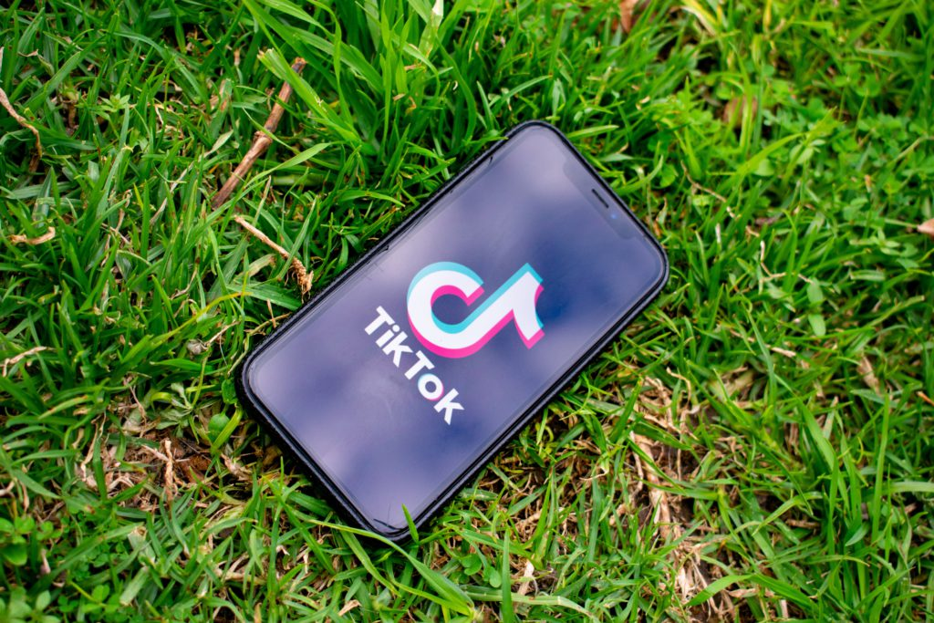 Phone with TikTok app laying in grass