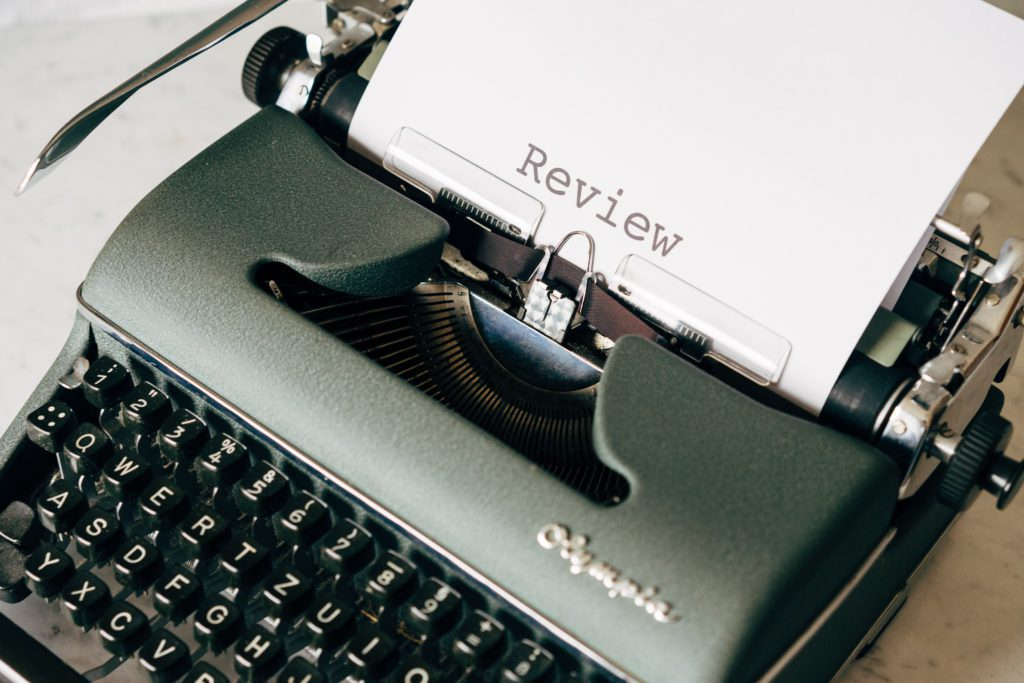 "A typewriter with the word ""Review"" written on a paper"